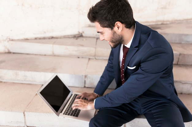 High angle man sitting on stairs with laptop Free Photo