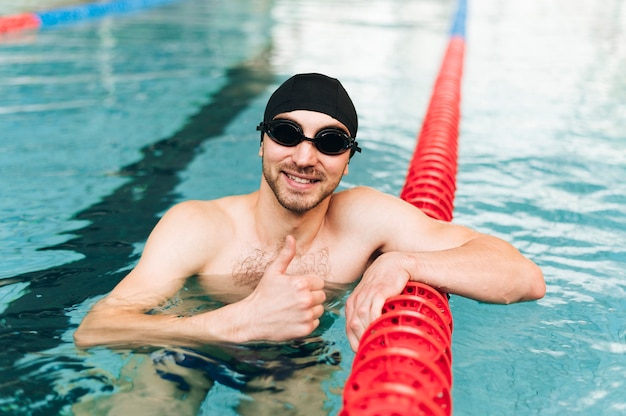High angle man in swimming pool showing ok sign Free Photo