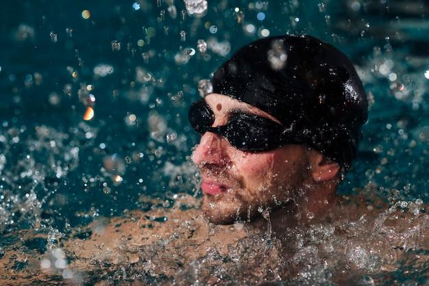 Uomo alto angolo con occhiali e cuffia nuoto Foto Gratuite