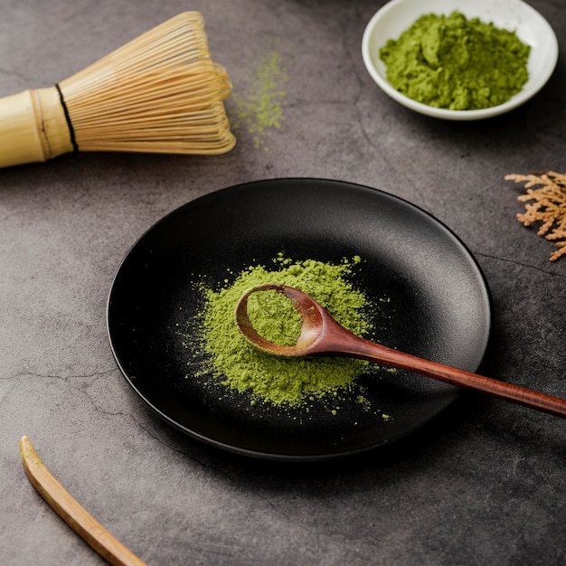 High angle of matcha tea powder on plate with wooden spoon Free Photo