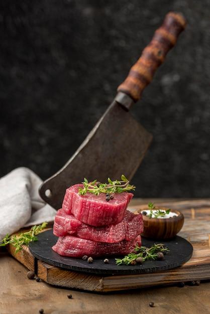 Alto angolo di carne su ardesia con erbe e mannaia Foto Gratuite