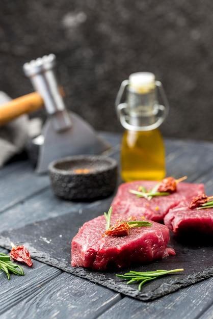Alto angolo di carne con olio ed erbe Foto Gratuite