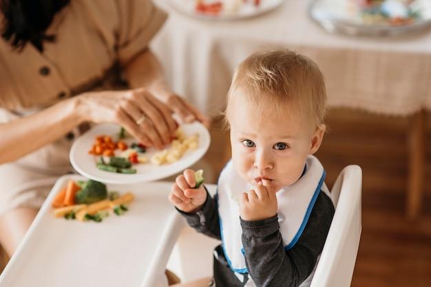 Мать под высоким углом помогает ребенку выбрать, какую еду съесть Premium Фотографии