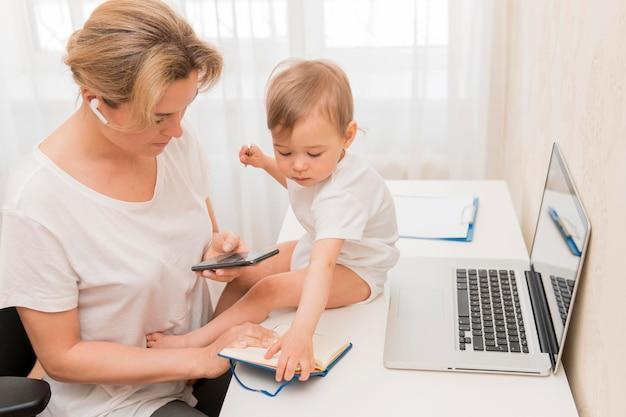 Madre dell'angolo alto che esamina telefono e bambino sullo scrittorio Foto Gratuite