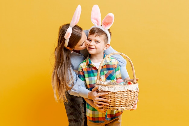 High angle mother and son with basket of painted eggs Free Photo