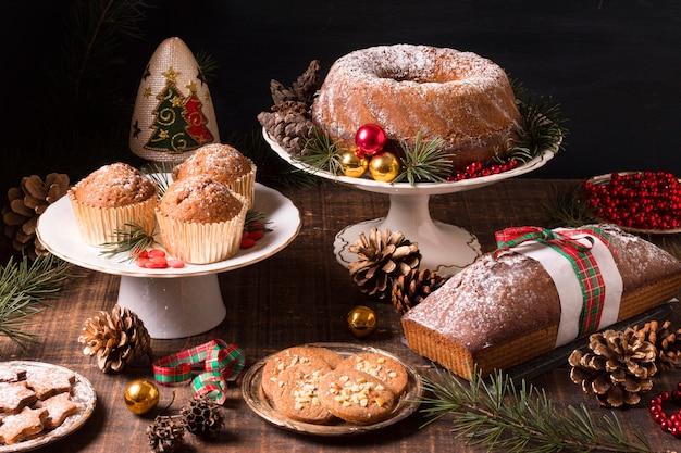 松ぼっくりと赤いベリーのクリスマスデザートの高角度の品揃え 無料写真