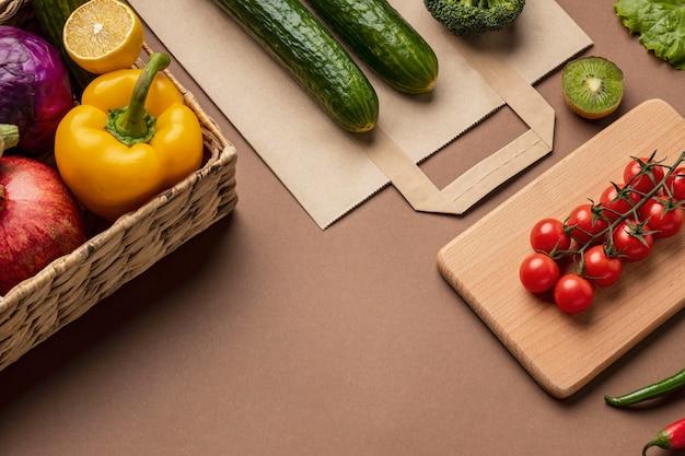 食料品の袋と有機野菜のバスケットの高角度 無料写真