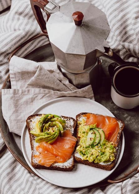 Бутерброды на завтрак с лососем и авокадо под высоким углом в постели Бесплатные Фотографии