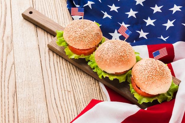 Высокий угол бургеры с американскими флагами на деревянной поверхности Бесплатные Фотографии