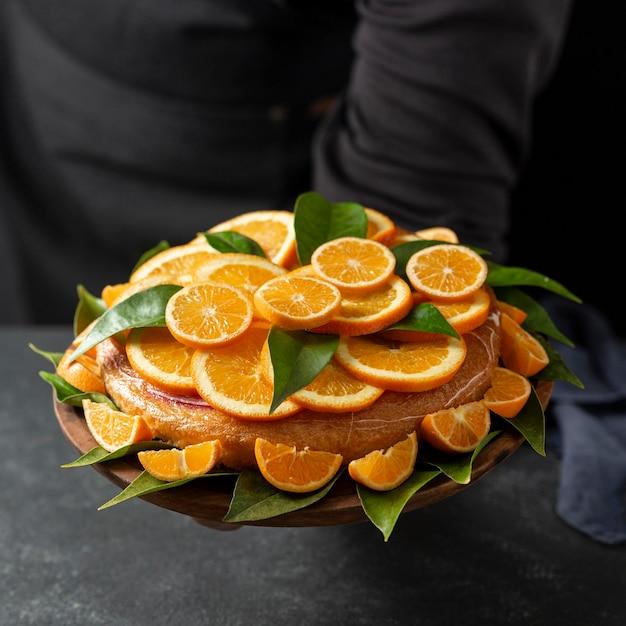 オレンジ色のスライスと葉を持つケーキの高角度 無料写真