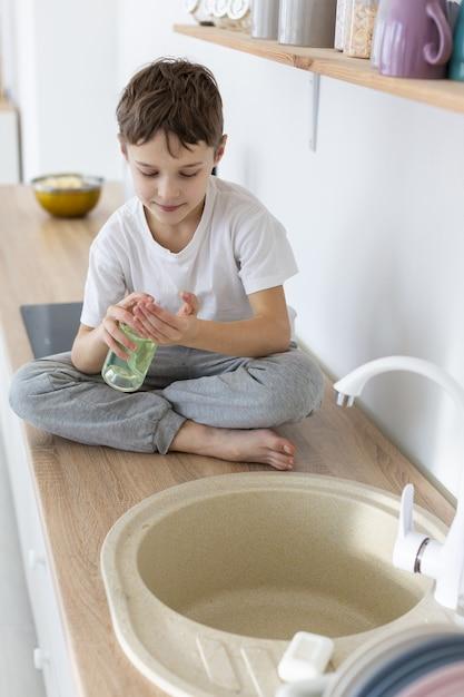 液体石鹸を使用する子供の高角度 無料写真