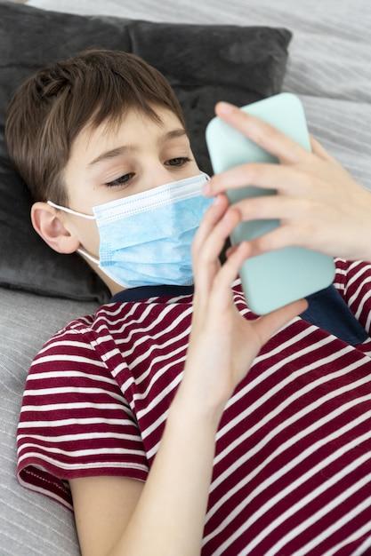 スマートフォンを保持している医療用マスクを持つ子供のハイアングル 無料写真
