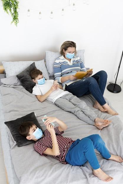 医療用マスクと本を読んでいる母親と一緒にベッドで子供たちの高角度 無料写真