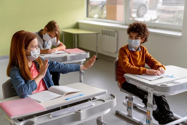教室で距離を保つ医療用マスクを持った子供たちの高角度 無料写真