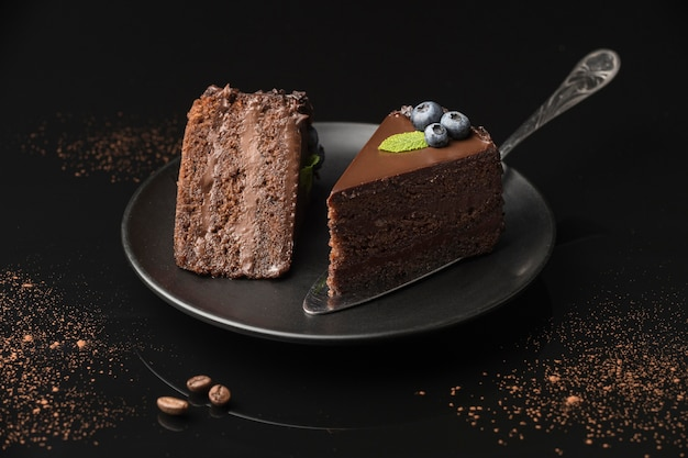 へらでプレート上のチョコレートケーキスライスの高角度 Premium写真