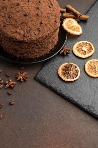 Высокий угол шоколадного торта с какао-порошком и сушеными цитрусовыми Бесплатные Фотографии