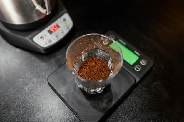 Высокий угол кофейного стакана на весах с чайником Бесплатные Фотографии