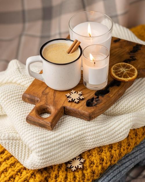 キャンドルとシナモンスティックと一杯のコーヒーの高角度 Premium写真