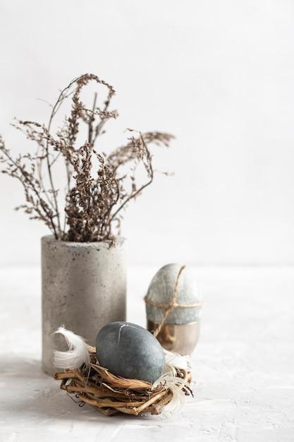 Высокий угол пасхального яйца в птичьем гнезде с вазой с цветами Бесплатные Фотографии