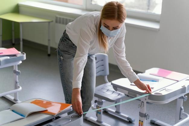 Учительница в медицинской маске под высоким углом измеряет расстояние между скамейками в классе Бесплатные Фотографии