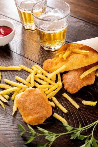 Высокий угол рыбы с жареным картофелем в бумажном конусе с пивом Бесплатные Фотографии