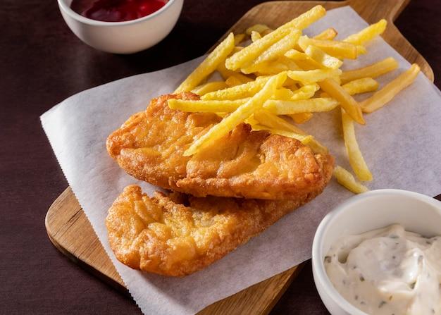 Большой угол рыбы с жареным картофелем на разделочной доске с соусами Premium Фотографии