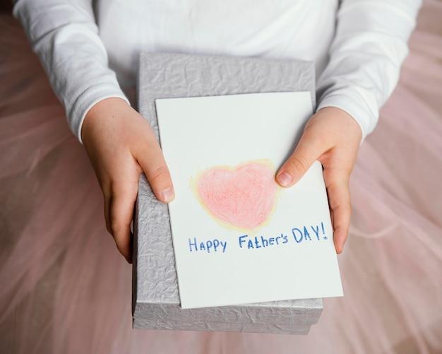 아버지의 날 선물과 카드를 들고있는 소녀의 높은 각도 무료 사진