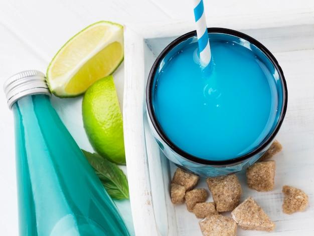 Высокий угол стакана безалкогольного напитка с бутылкой и соломинкой Бесплатные Фотографии