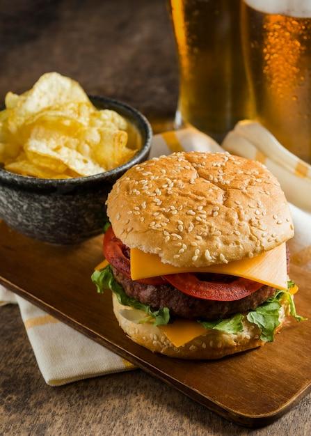 チーズバーガーとチップスとビールのグラスの高角度 無料写真