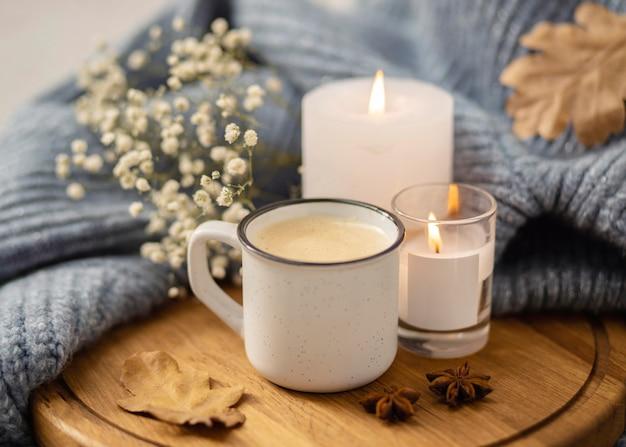 커피와 스웨터 한잔과 함께 조명 된 촛불의 높은 각도 무료 사진