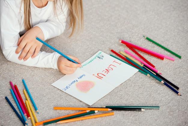 Высокий угол маленькой девочки, держащей чертежную карточку на день отца Бесплатные Фотографии
