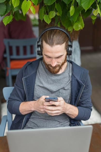 Высокий угол человека на городской террасе с ноутбуком и смартфоном Бесплатные Фотографии