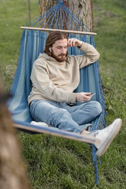 スマートフォンでハンモックで男のハイアングル 無料写真