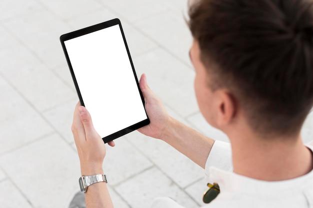 Высокий угол зрения человека, смотрящего на планшет с копией пространства Бесплатные Фотографии