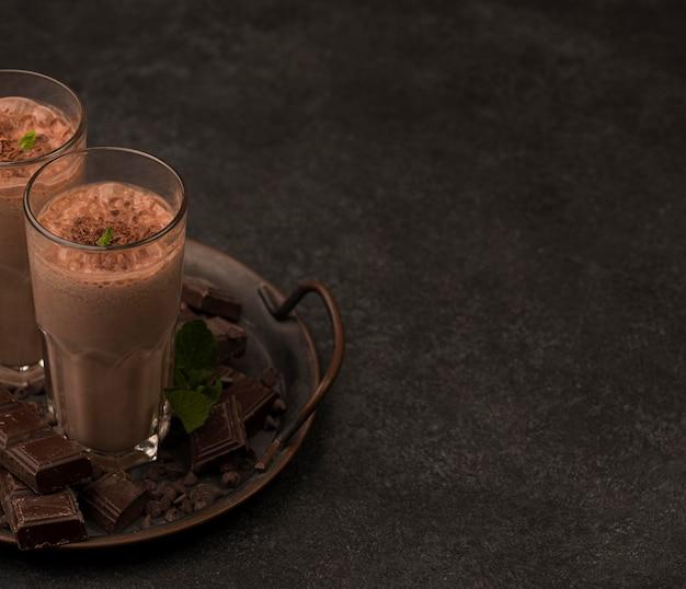 Высокий угол бокалов для молочных коктейлей на подносе с шоколадом и копией пространства Бесплатные Фотографии