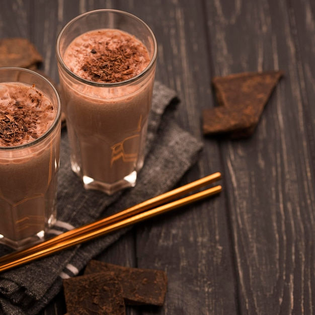 Высокий угол стакана для молочного коктейля с соломкой и шоколадом Бесплатные Фотографии