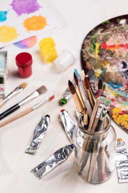 Высокий угол рисования кистей в банке и палитре Бесплатные Фотографии
