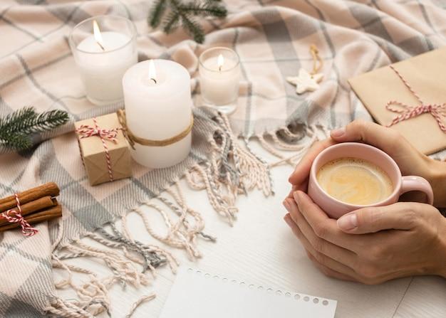 毛布とキャンドルでマグカップを持っている人の高角度 無料写真