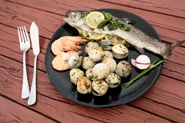 魚とアサリのプレートの高角度 無料写真