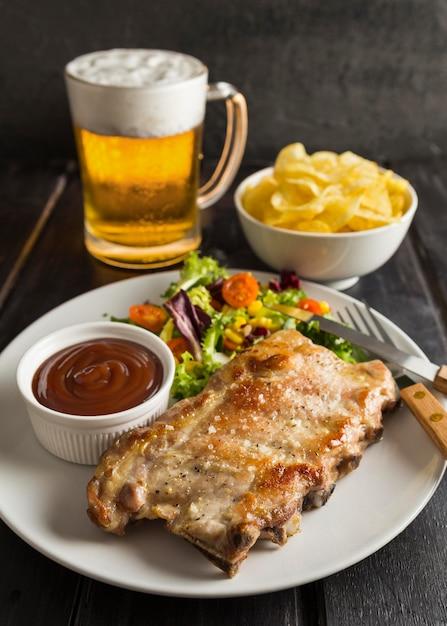 ビールとチップスを添えたプレート上の高角度のステーキ 無料写真