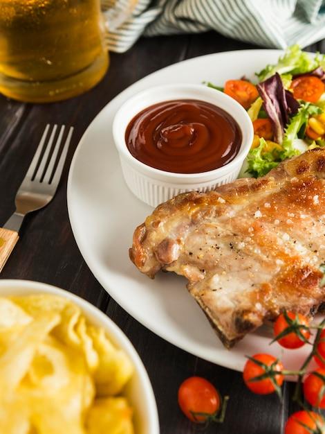 チップスとビールを添えたプレート上の高角度のステーキ 無料写真