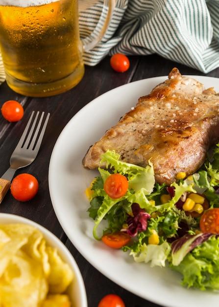 Высокий угол стейка на тарелке с салатом и бокалом пива Бесплатные Фотографии