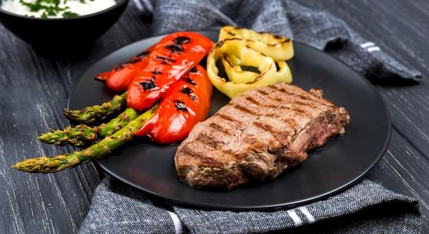 Высокий угол стейка на тарелку с овощами Premium Фотографии