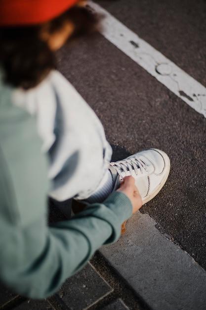 Подросток завязывает шнурки на открытом воздухе под высоким углом Бесплатные Фотографии