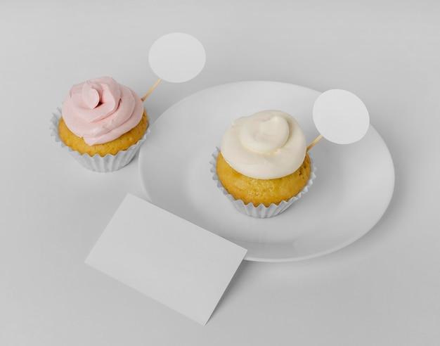 パッケージとプレート付きの2つのカップケーキの高角度 無料写真
