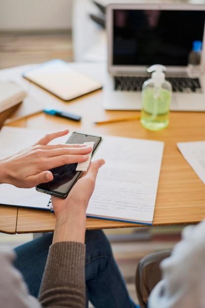 Высокий угол женщины дезинфицирует свой смартфон перед уроком Бесплатные Фотографии