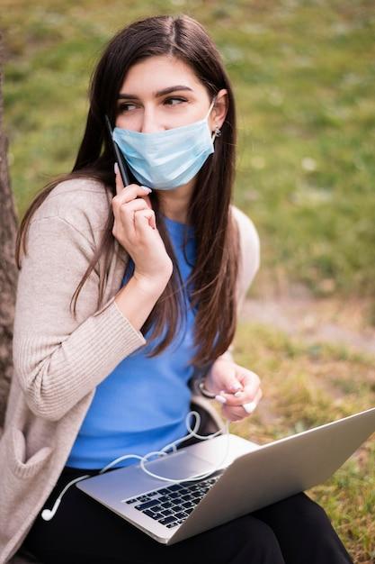 ラップトップで屋外作業医療マスクを持つ女性の高角度 無料写真