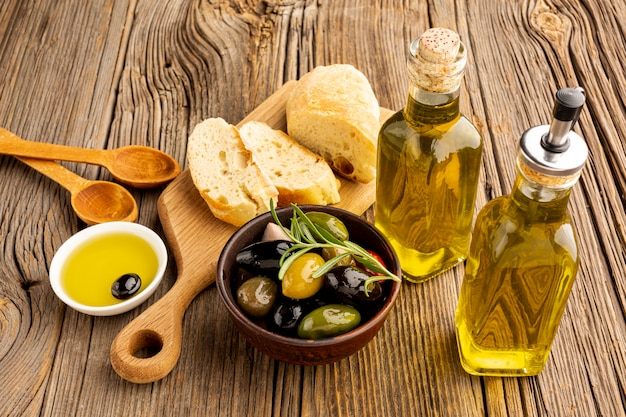 High angle olives mix bread and oil bottles Free Photo
