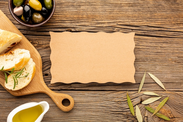 High angle olives mix bread and oil saucer with cardboard mock-up Free Photo