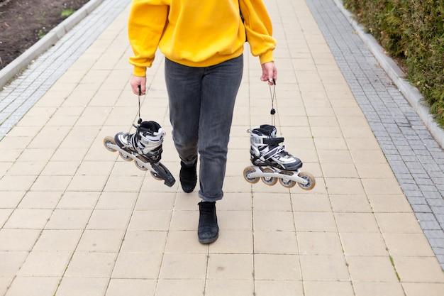 歩きながらローラーブレードを保持している女性に高角度 無料写真
